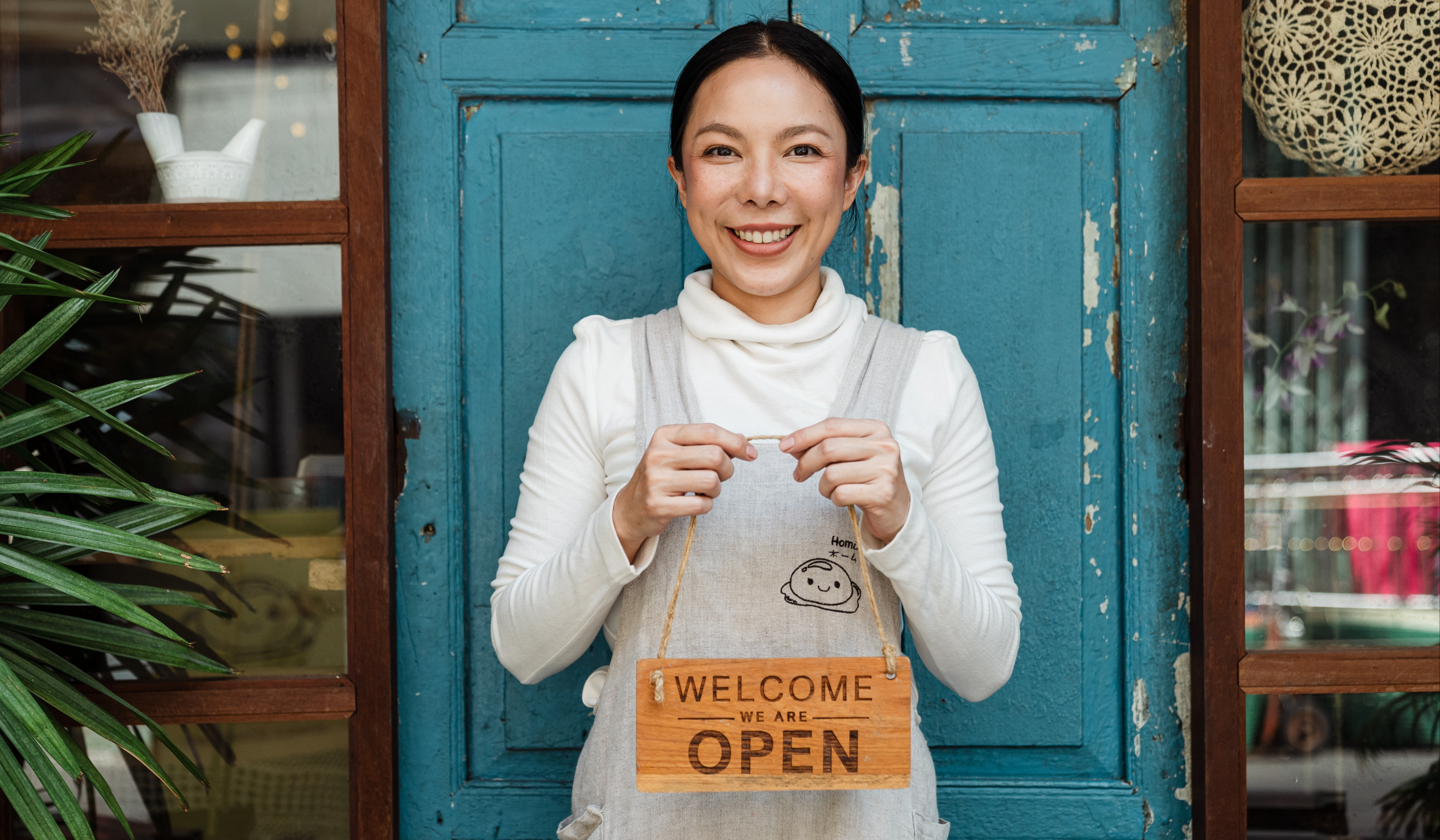 """a smiling woman holding a sign that says """"welcome, we are open"""""""